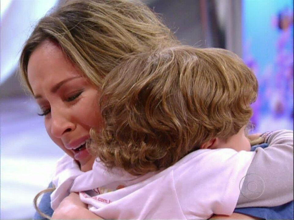 Ela se emociona com a homenagem pelo Dia das Mães. Grávida de Rafael, chora com as presenças do primogênito, Davi, e da mãe, Ilma