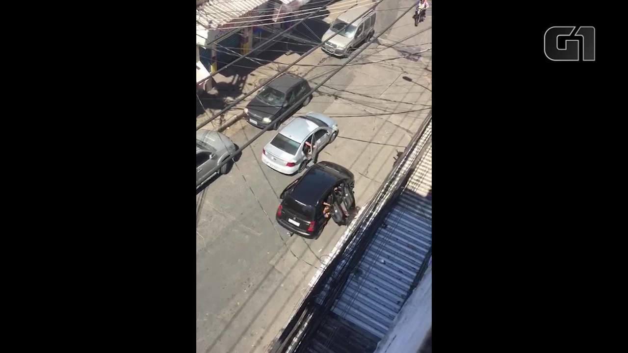 Criminosos armados passam ao lado de viaturas da UPP