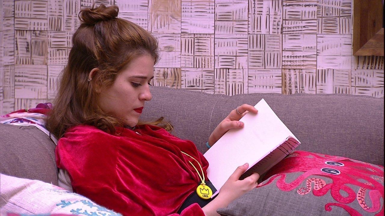 Ana Clara lê no sofá ao lado de Breno