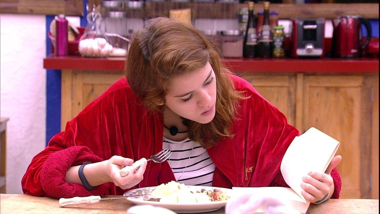 Ana Clara almoça e lê um livro na cozinha