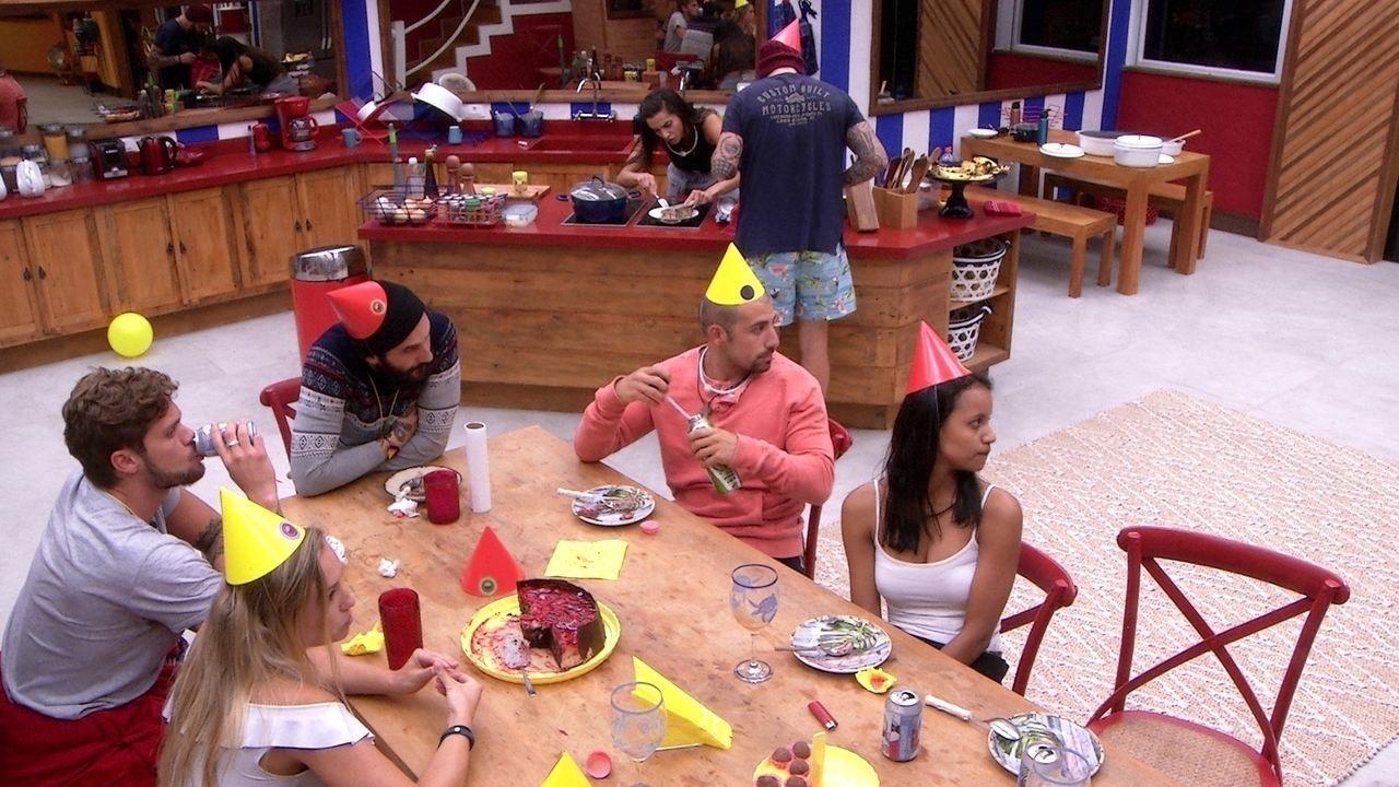Paula esquenta comida enquanto brothers conversam e comem bolo