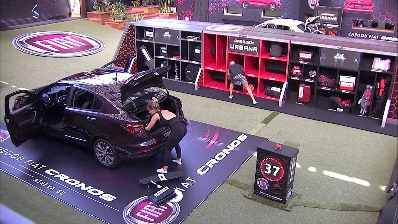 Kaysar e Jéssica organizam itens no bagageiro do Fiat Cronos Vermelho Marsala