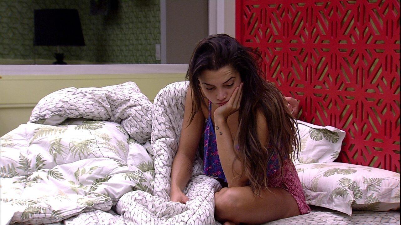 Paula fica sentada na cama de casal do Quarto Tropical