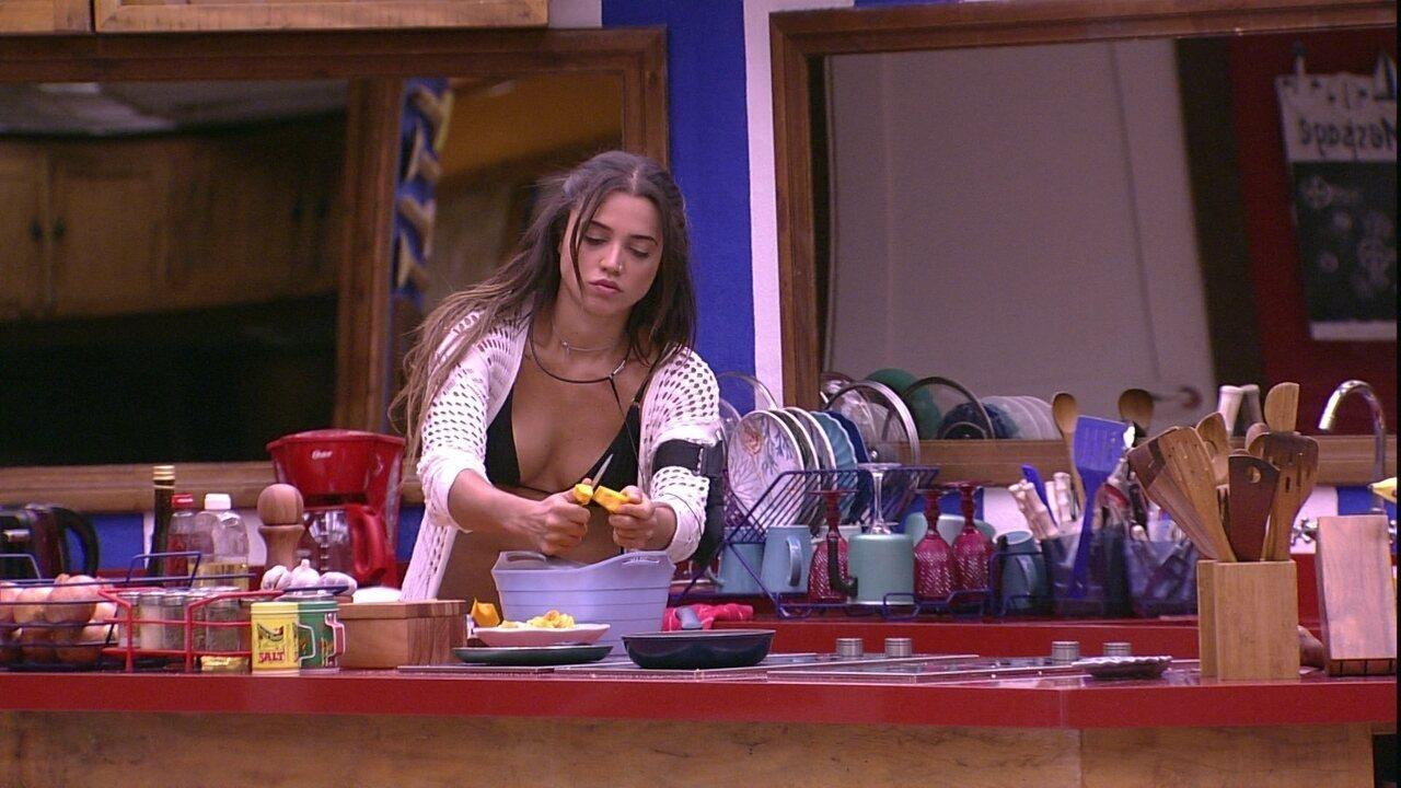 Paula corta abóbora na cozinha