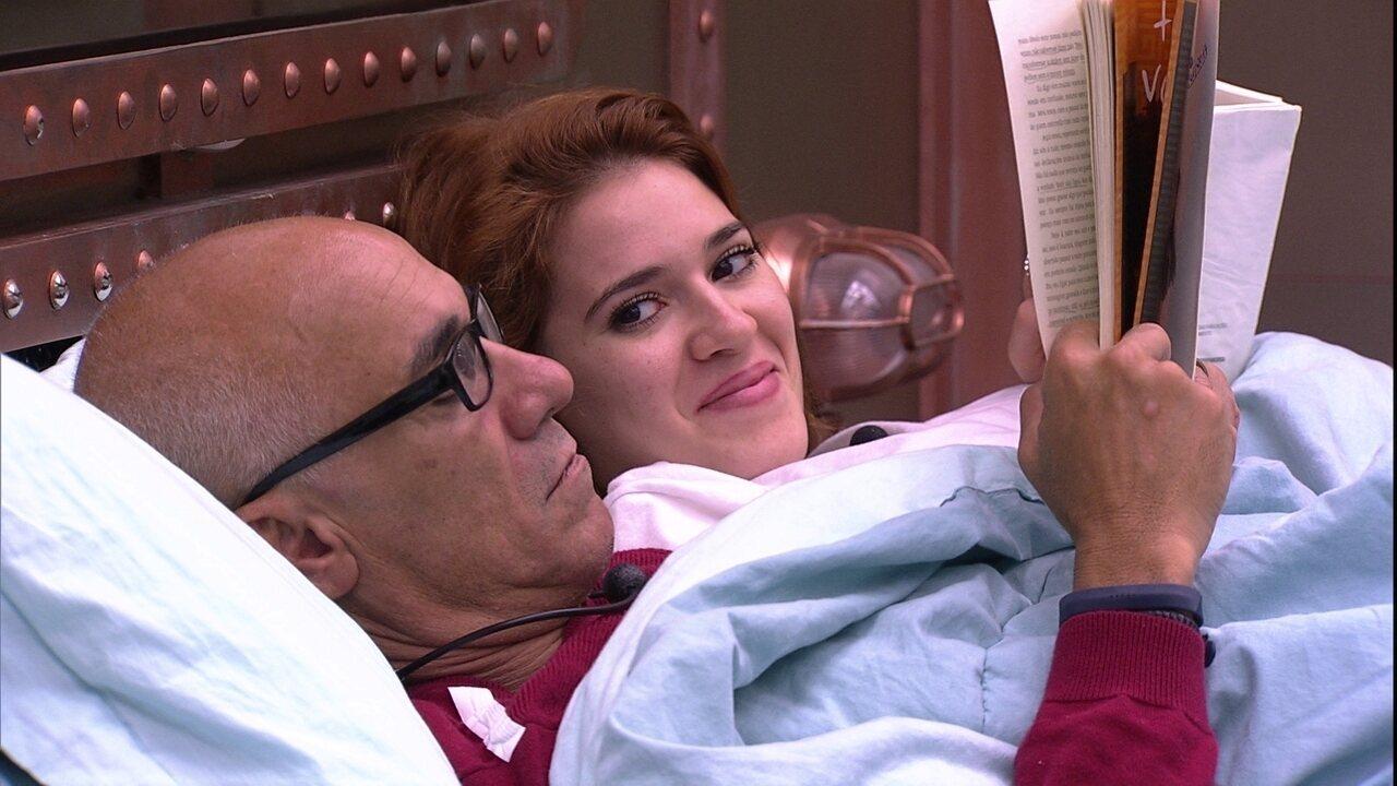 Ana Clara ri ao olhar para Ayrton com livro na mão