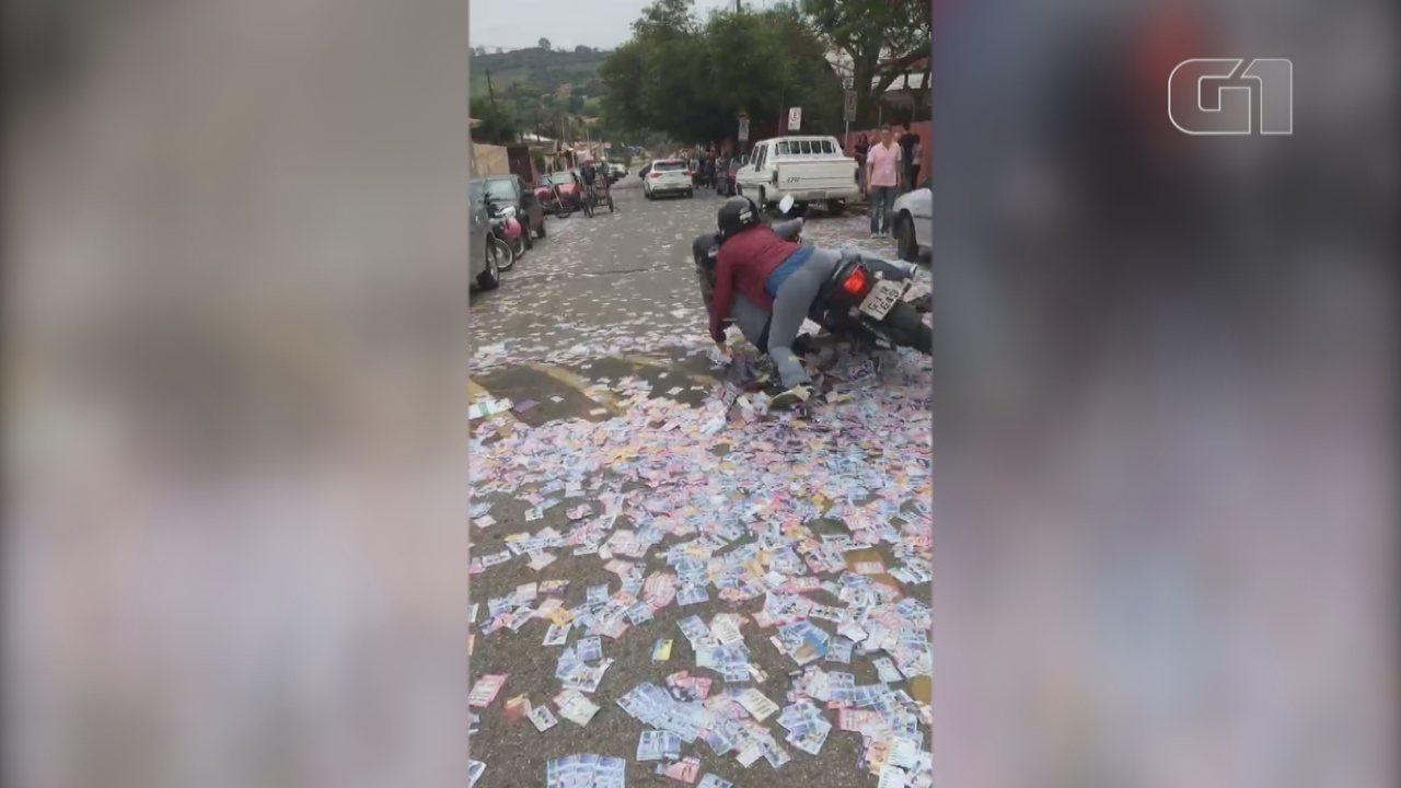 Motociclista cai em rua forrada de santinhos