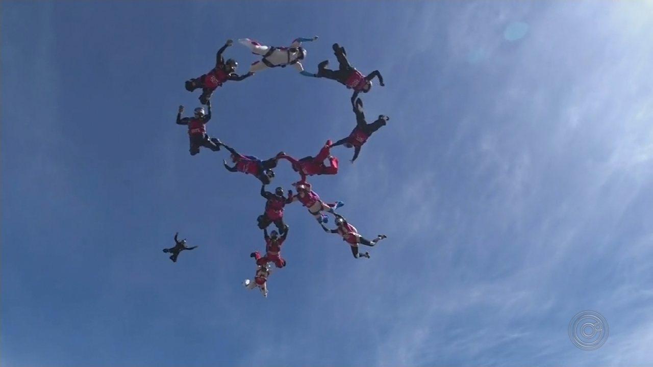 Mulheres paraquedistas formam símbolo do 'Outubro Rosa' no céu durante salto