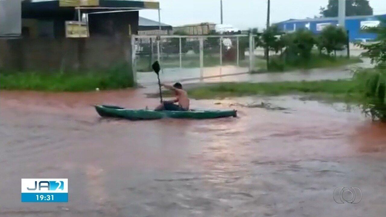 Morador é visto em caiaque remando em rua alagada, em Goiás