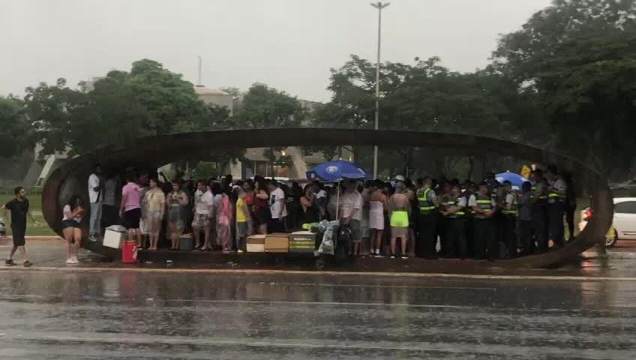 Foliões se abrigam da chuva em parda de ônibus no centro de Brasília