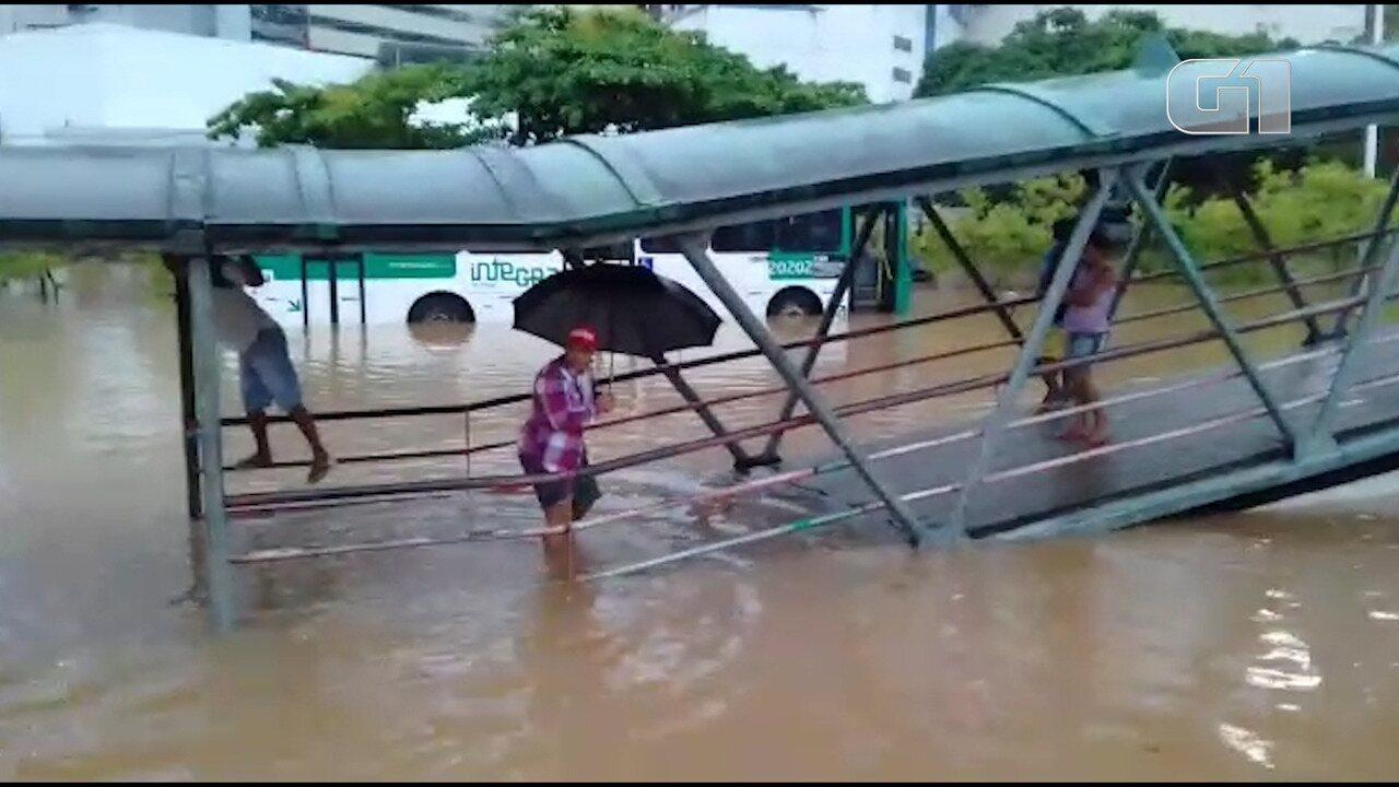 Pedestres andam no meio da água em região alagada na Avenida ACM