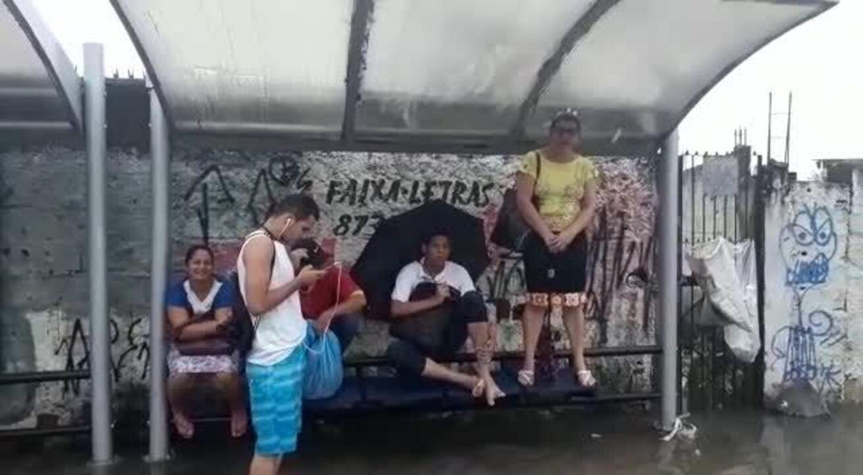 Passageiros de ônibus aguardam transporte em parada alagada na Zona Sul do Recife