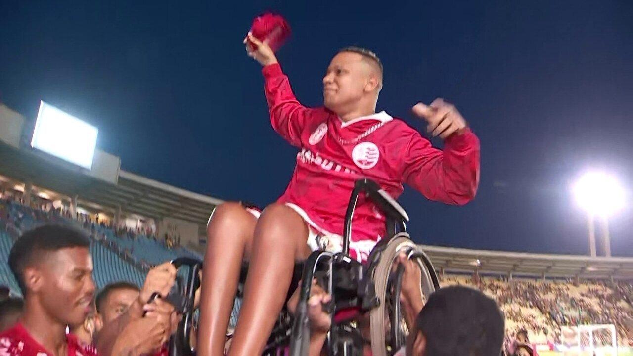 Torcedor cadeirante é suspenso por jogadores do Náutico, no campo, após conquista