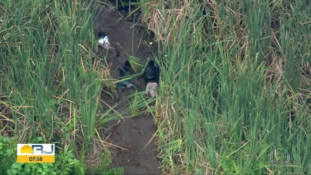 Homens fogem pela lama durante operação policial na Cidade de Deus