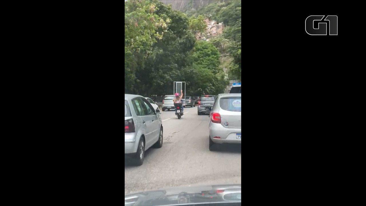 Mulher é flagrada na garupa de moto carregando uma janela